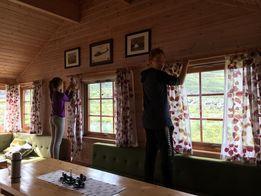 Nyvaska gardiner skal henges opp, i jubileumshytta, på Rosta. Eline og Kristian på 13år tar dugnads jobben. August 2018
