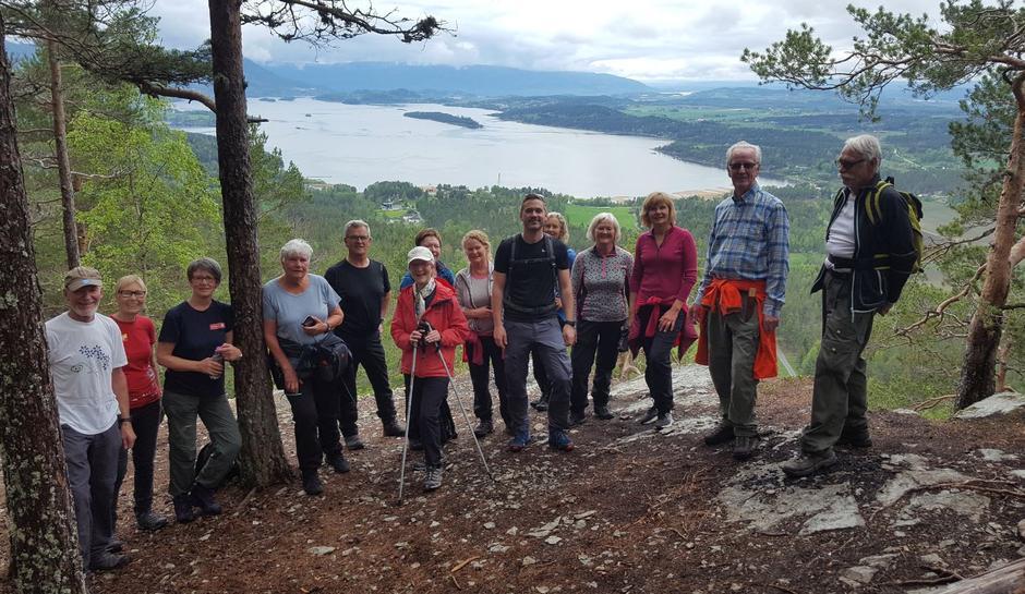 Deltakerne på turen med utsikten fra Tiurtoppen mot Steinsfjorden.