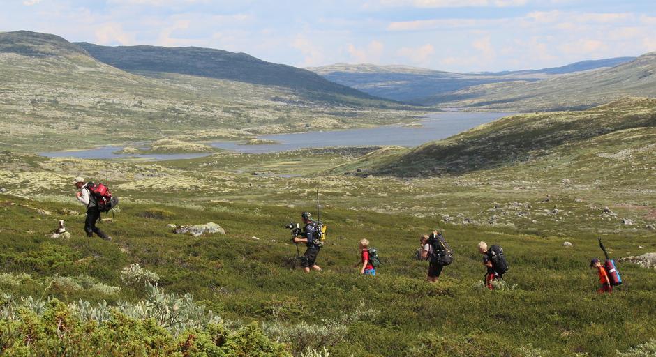 Lars Monsen og den lange rekka med turfolk passerar framfor Nedre Hein på Hardangervidda.