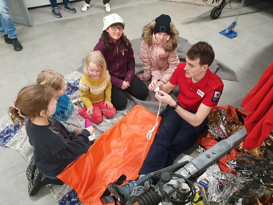 Kristian fra Røde Kors viser barne hvhilket utstyr de kan bruke når de skal spjelke en fot.