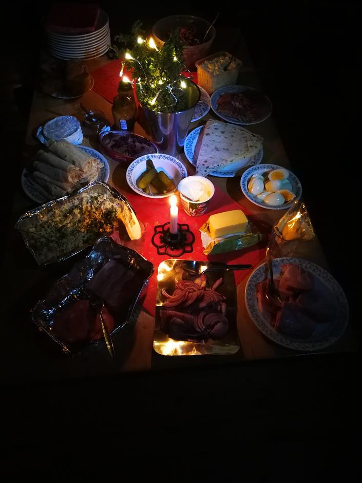 Eit fyldig matbord med mykje god mat. Merk deg juletreet midt på bordet.