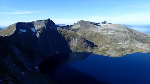 Fra Prosten ser vi ned i det mørkeblå Svartevatnet. Her sees også Svartevasstinden, Trolltinden og Midttinden.