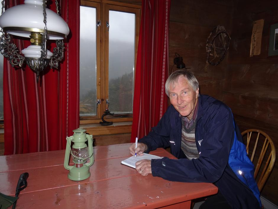 Ivar Eidsheim skriv i gjesteboka på Fjelde gard. Tusen takk for oss!