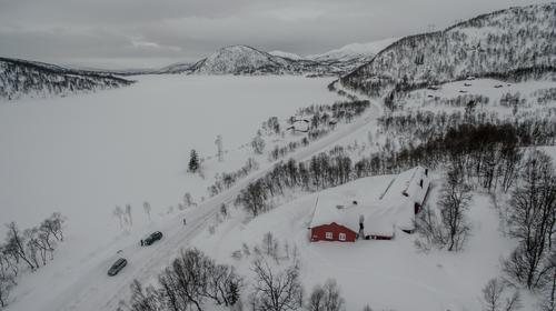 Dronebilde av hytta som ligger like ved veien