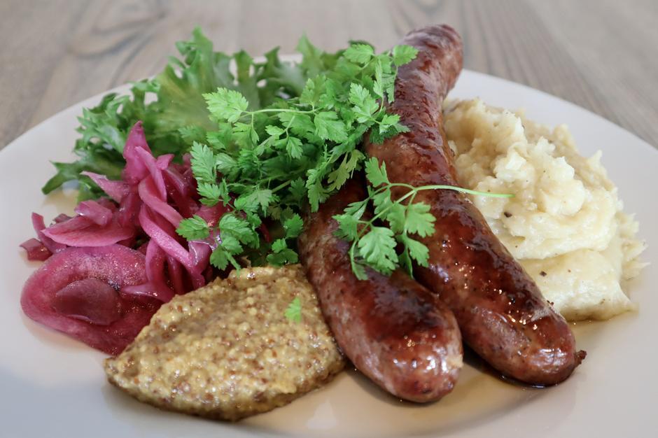 Pølser fra Hovden, servert med potetpurè, syltet løk og sennep