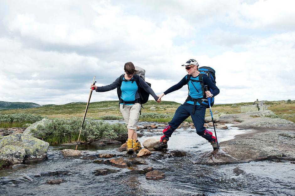 Bildet viser to personer som krysser en liten elv. En ledsager går foran og en person med synshemming holder i hånda. Begge bruker gå stav i den andre hånden.