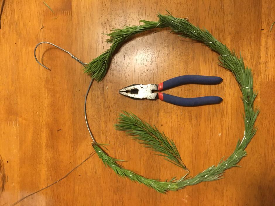 Dekk kransen med furukvister ved å surre tråden rundt.