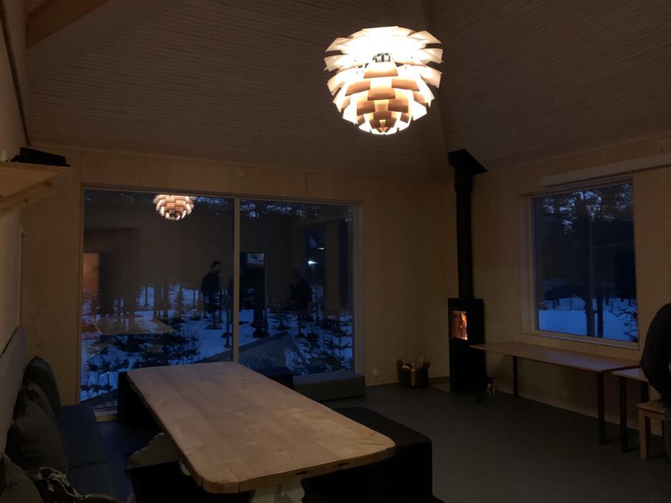 Oppholdsrommet i det nye sovehuset har fått konglelampe og peisovn.