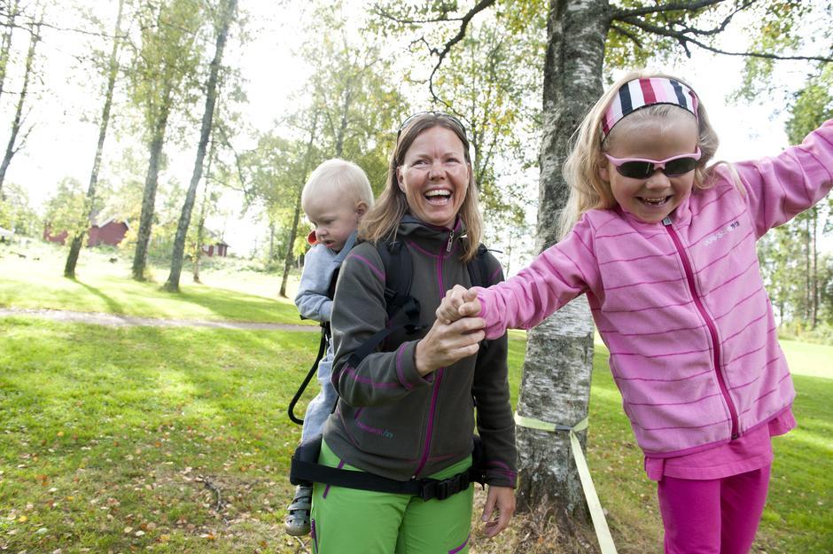 Nora Eriksen prøver seg på slakk line, godt hjulpet av mamma Evy Eriksen. Lillebror Ludvik sitter godt i bæremeisen.
