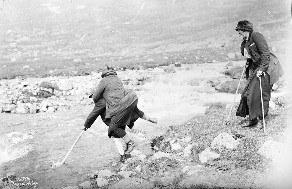 En kvinne bæres over en elv i 1914.