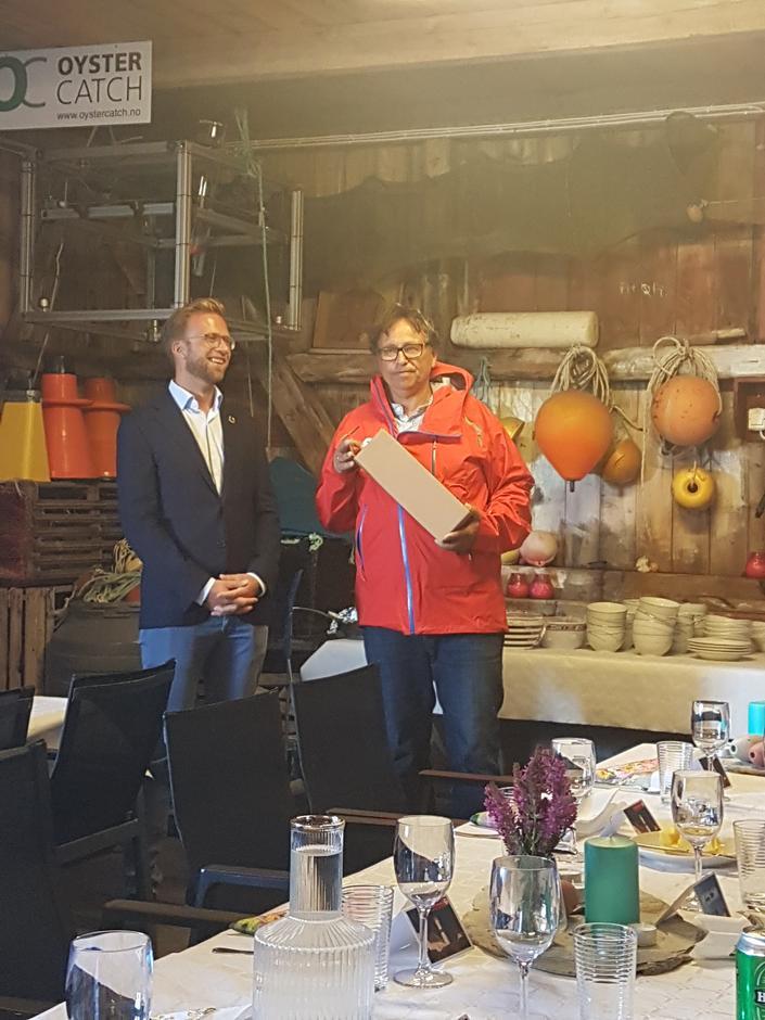 Styreleder i AAT Svein Hjorth-Olsen overrekker digitaliseringsminister Nikolai Astrup en kopi av Store Torungen fyr