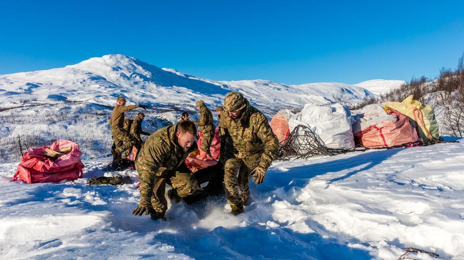 Drahjelp: Leading Hand (korporal) Watson (t.v.) får hjelp fra en medsoldat til å dra den tunge sekken langs snøen.