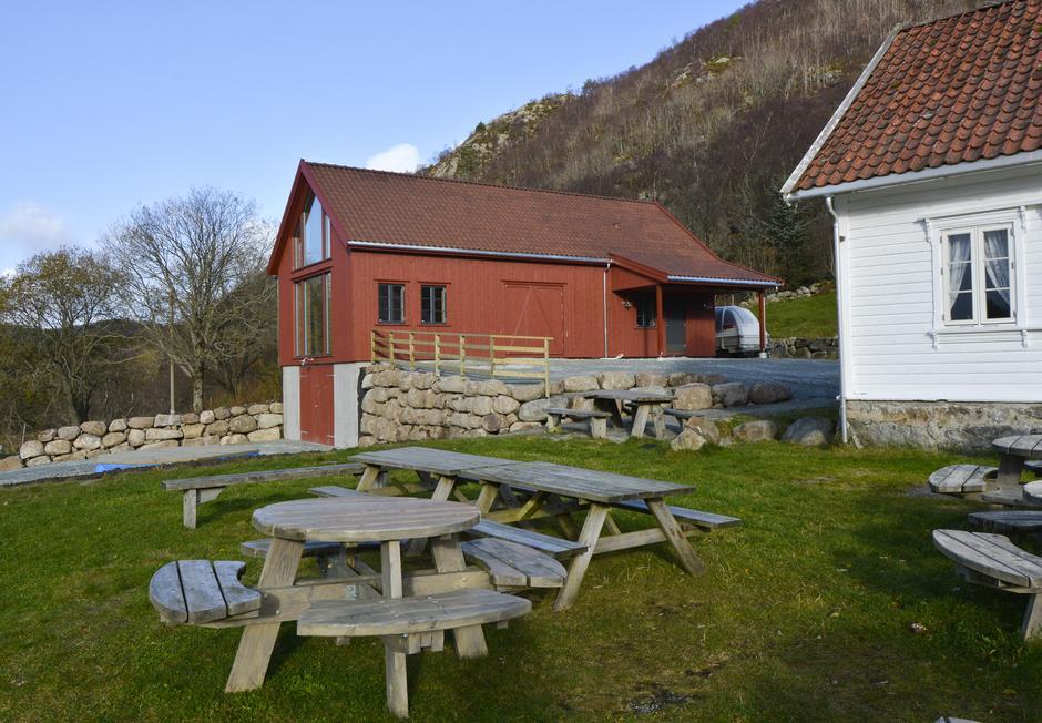 Fotoutstillingen er i den røde låven like ved det hvite huset på Gramstad.