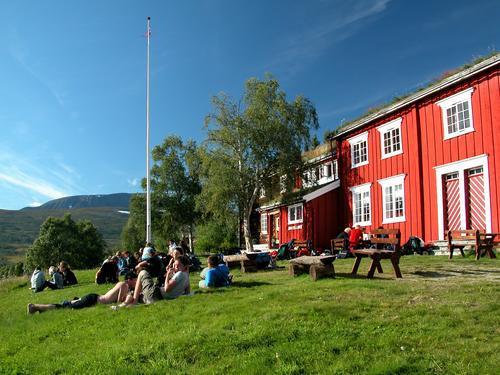 Gjevilvasshytta er rødmalt, med et stort grønt tre ved siden av.  Hytta ble kåret til Norges fineste betjente hytte i 2020.