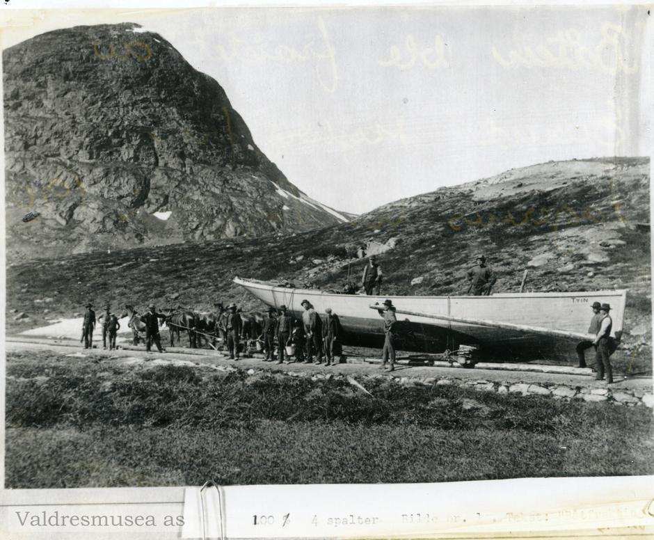 LETT ANKOMST: Å frakte motoriserte rutebåter til fjells var et svare slit, til gjengjeld gjorde pionérinnsatsen fjelleventyret lett tilgjengelig for hundretusenvis av fjellvandrere. Her er det motorbåten Tyin som rulles på stokker opp mot Båtskaret og Bygdin - oppover fire mil med motbakke fra Fagernes. Året er 1906.