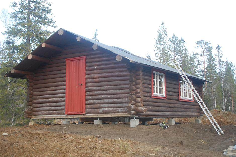 Liten tømmerhytte på plass på ny tomt i Vera