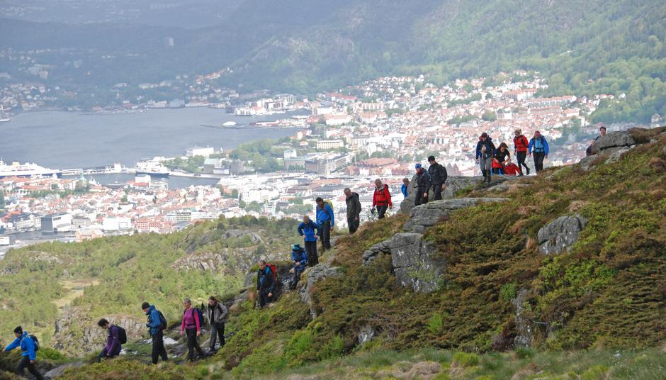 The 7-Mountains Hike in Bergen. Hikers on their way down from the top of Mount Løvstakken in Bergen, Norway.