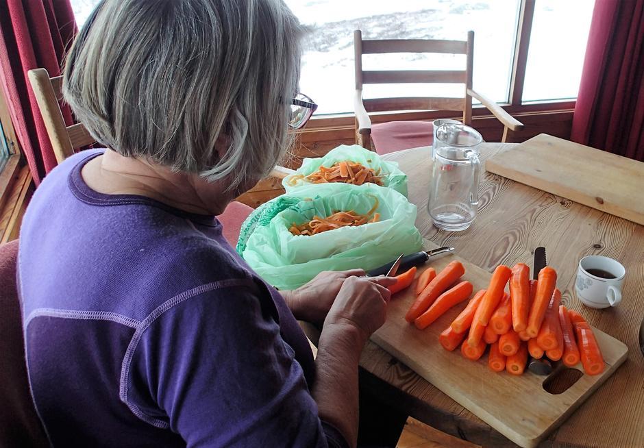 FORBEREDELSER: Middagforberedelsene starter etter frokost, og her er Bjørg Marit Bloch Johnsen i gang med skrelling av gulrøtter i store mengder.