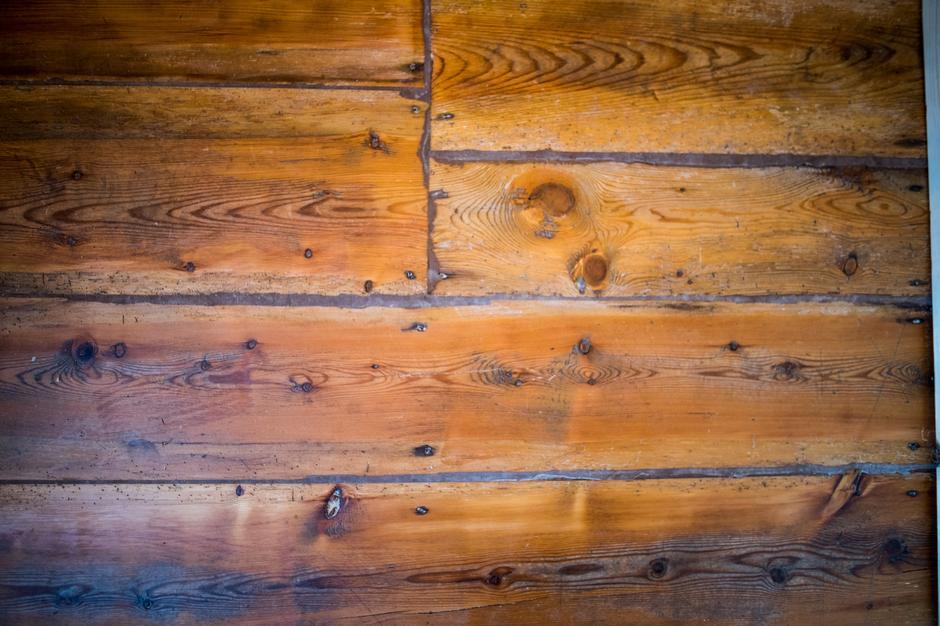 PATINA: Gulvet i hovedhuset er vakkert, og preget av tidens tann. De brede bordene er skåret av Johannes Bakken. Tømmeret er hentet ovenfor gården.