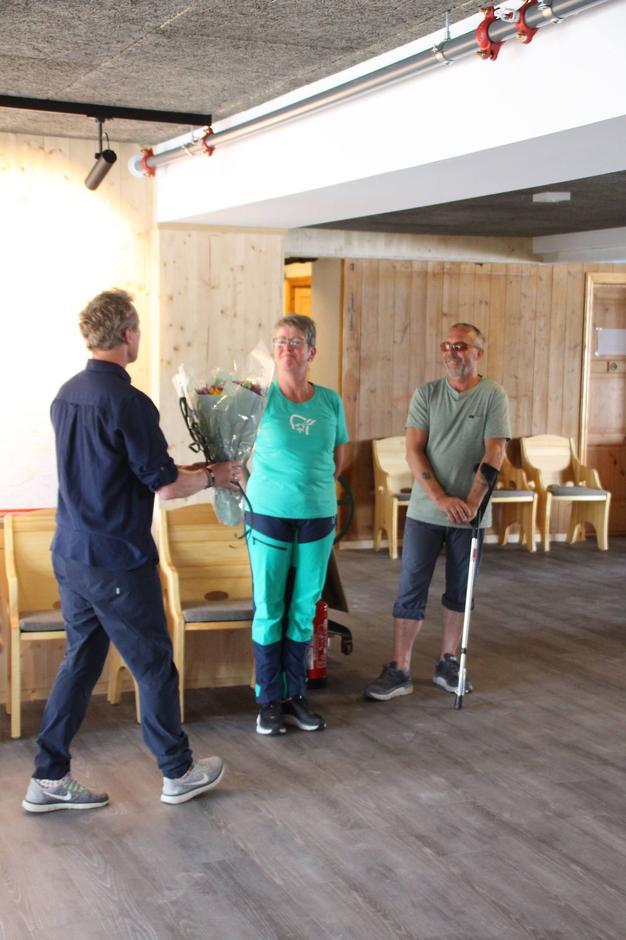 Hennig Hoff Wikborg overrekker blomster til bestyrerne som takk for tålmodigheten og alt de har bidratt med i byggeprosessen.