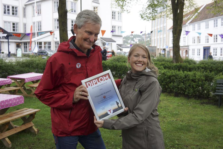 DNTs generalsekretær Nils Øveraas overleverer prisen til MDGs nasjonale talsperson Une Aina Bastholm under Arendalsuka.