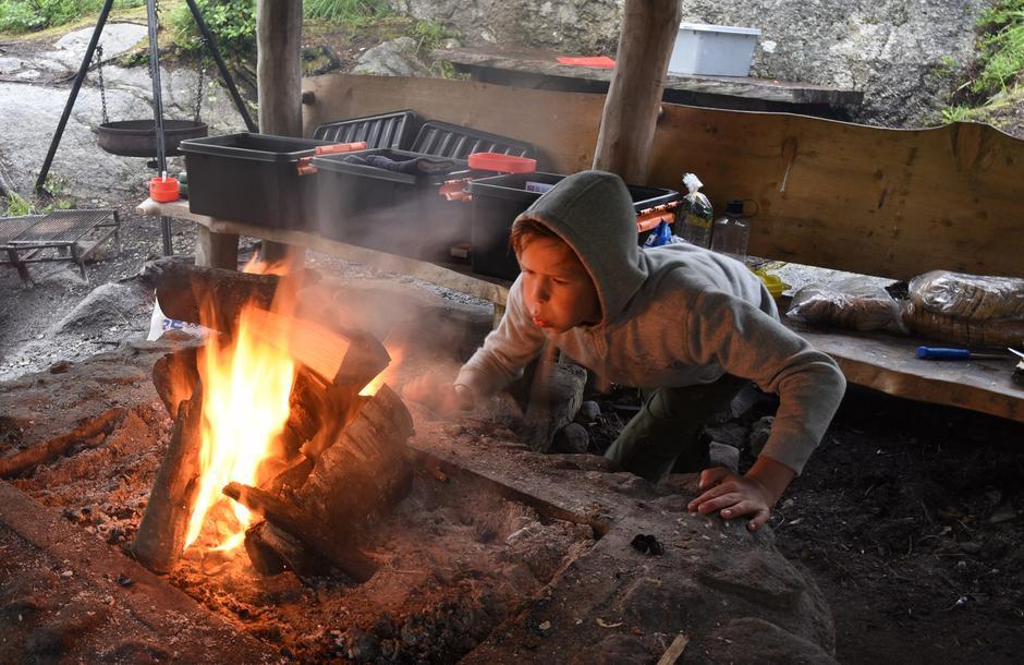 KOKKELERING: Mikkel er i full gang med å få fyr på bålet. Nesten all maten barna spiser lages ute.