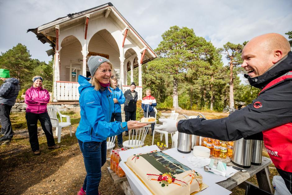Åse Turid Gjøen, frivillig og ressursperson i MRT, får sprette kaka sammen med Armin Sunde, turleder og representant fra Mesterbakeren.