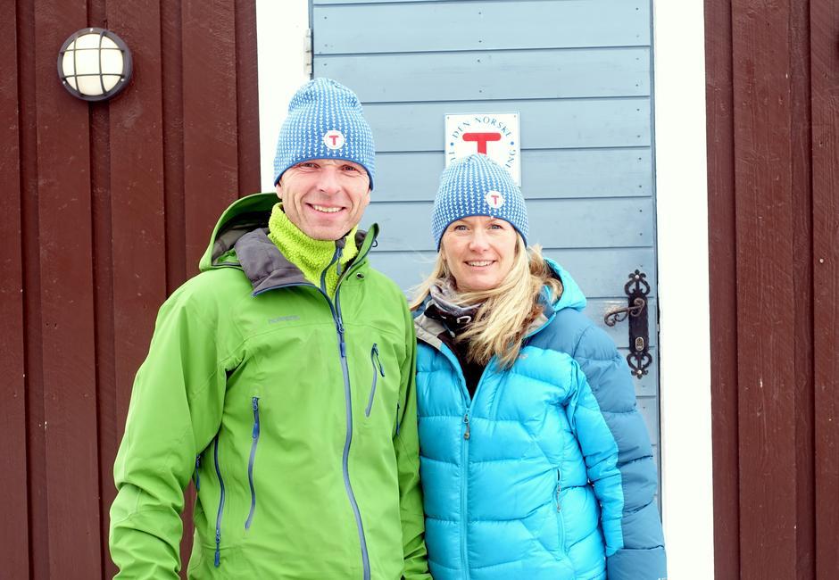Vertskapet Marit og John Wøllo utanfor inngangen til Geiterygghytta