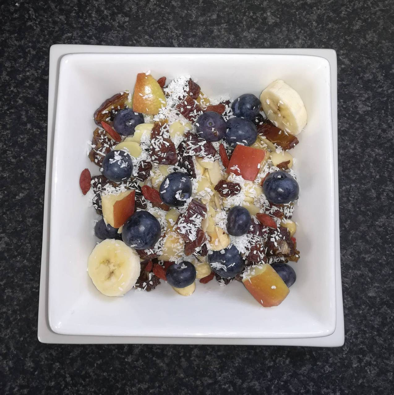 Untitled 2020-05-16 - Quick muesli with dried nuts, dried raisins, shredded coconut, fresh berries, bananas, apples and homemade coconut mylk