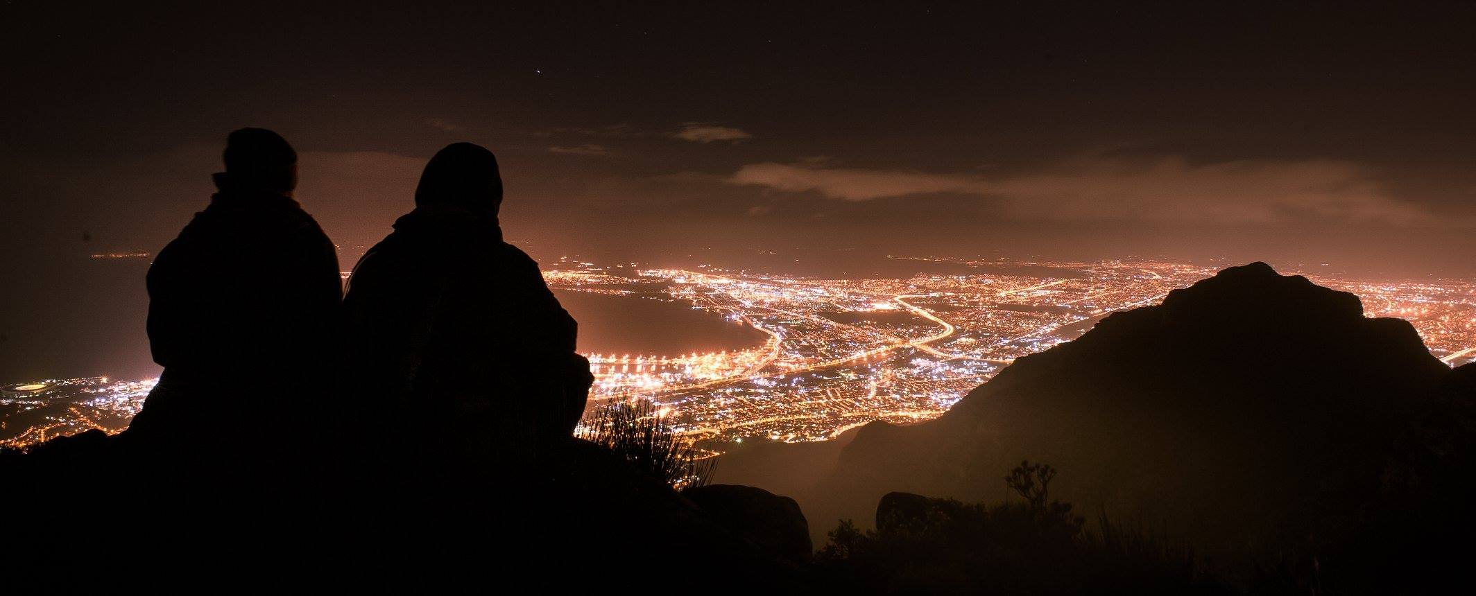 The silhouettes of two people overlooking Cape Town's Table Mountain at night.