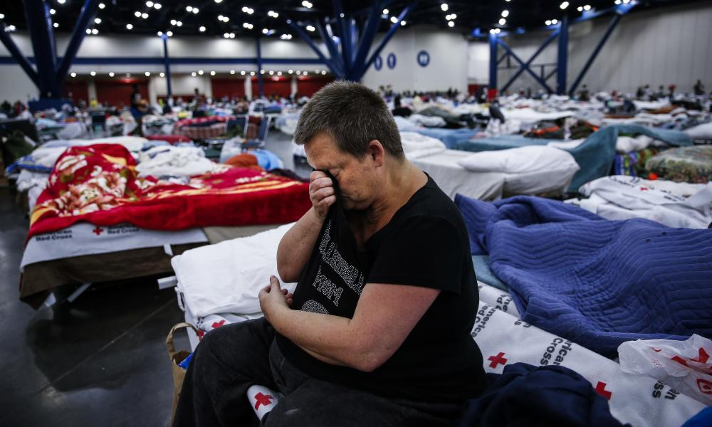 A woman wipes away tears as she sits on a cot at a center where nearly 10,000 people are taking shelter in Houston.