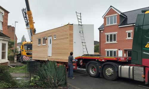A 'micro-home', designed to provide temporary accommodation for the homeless, being installed into a back garden in Worcester.