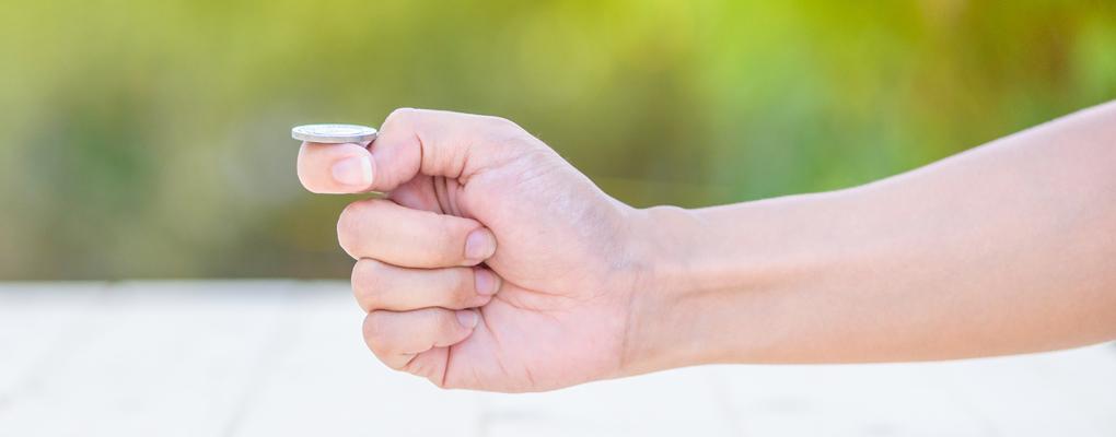 Eine Hand ist im Begriff, eine Münze zu werfen