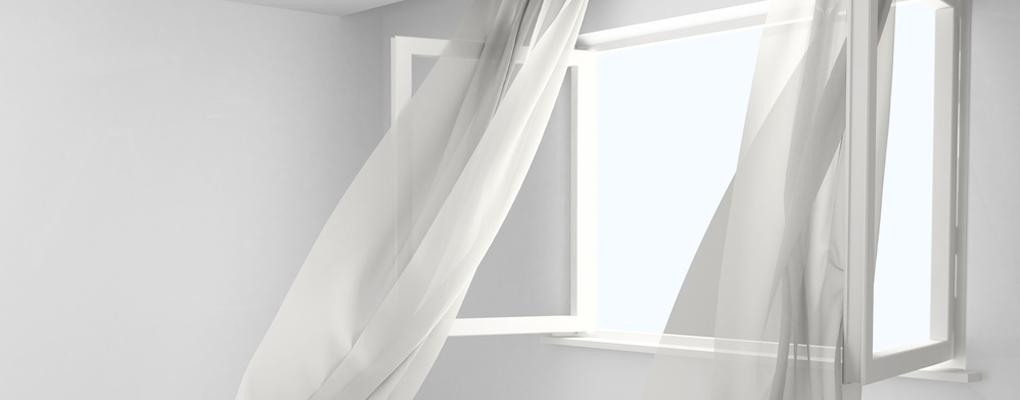 Ein offenes Fenster mit wehendem Vorhang