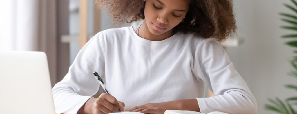 Ein Mädchen sitzt am Schreibtisch und macht Notizen