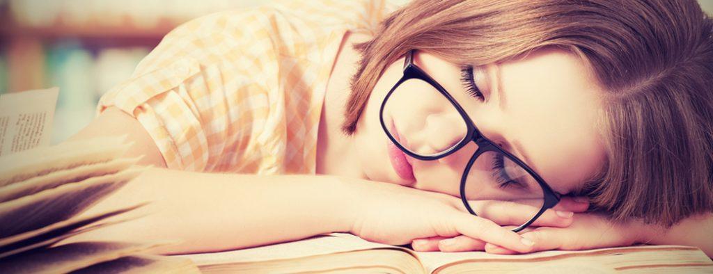 Ein Mädchen liegt mit dem Kopf auf dem Schreibtisch und schläft