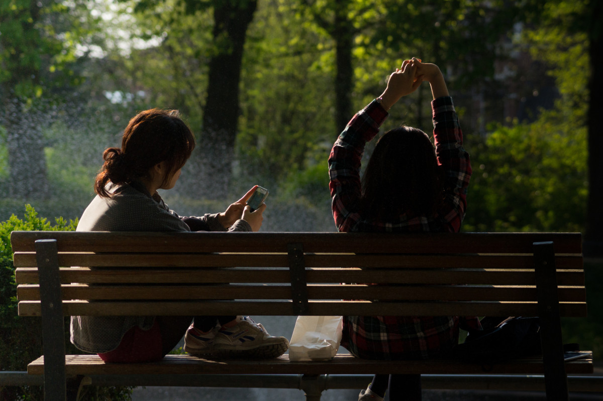 photograph picture of two women woman stretching on a park bench