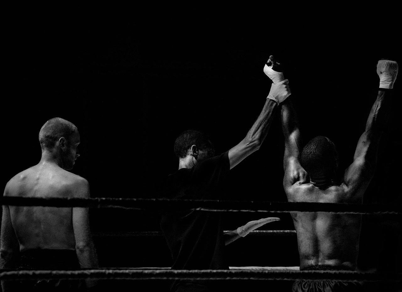 photograph picture of two boxers and a referee in the ring after a fight