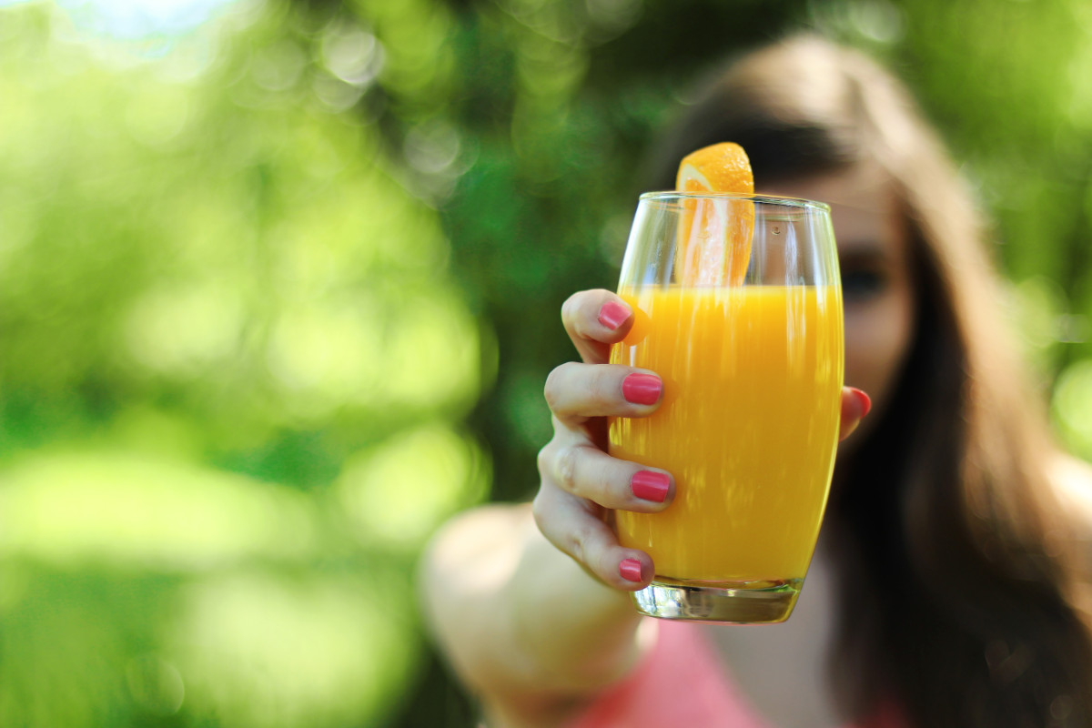 photograph picture of a woman offering a glass of orange juice