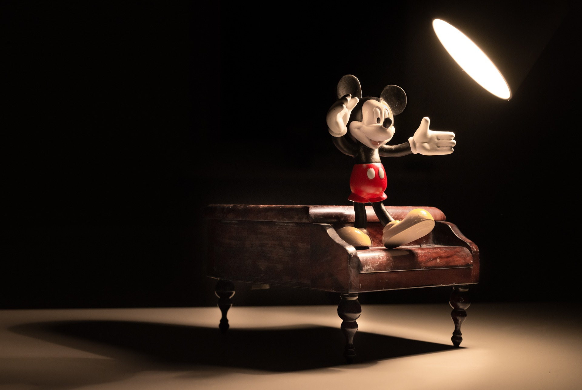 Photo of miniature Mickey Mouse figure on a piano.