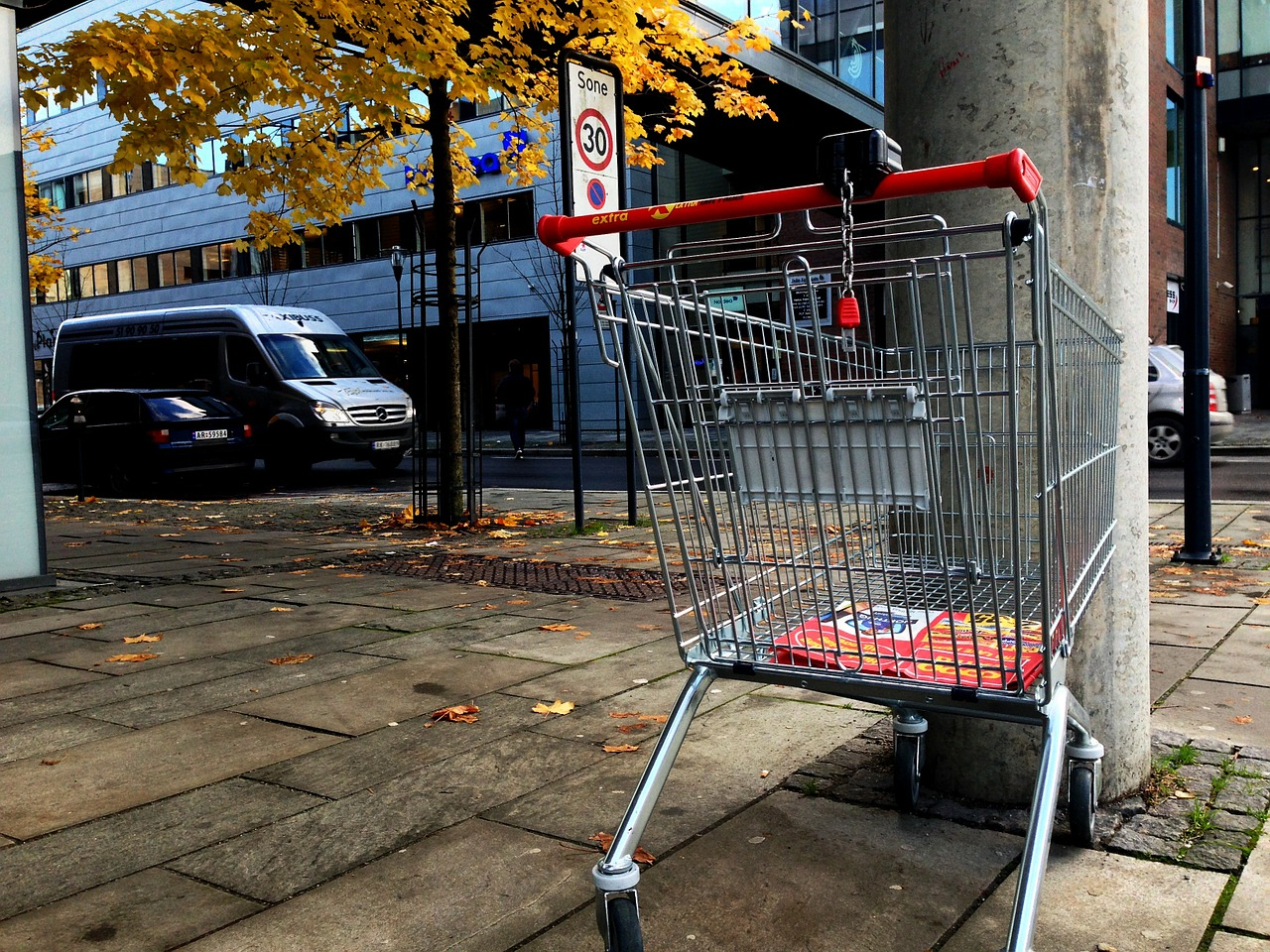 photograph picture of an empty shopping cart on the sidewalk