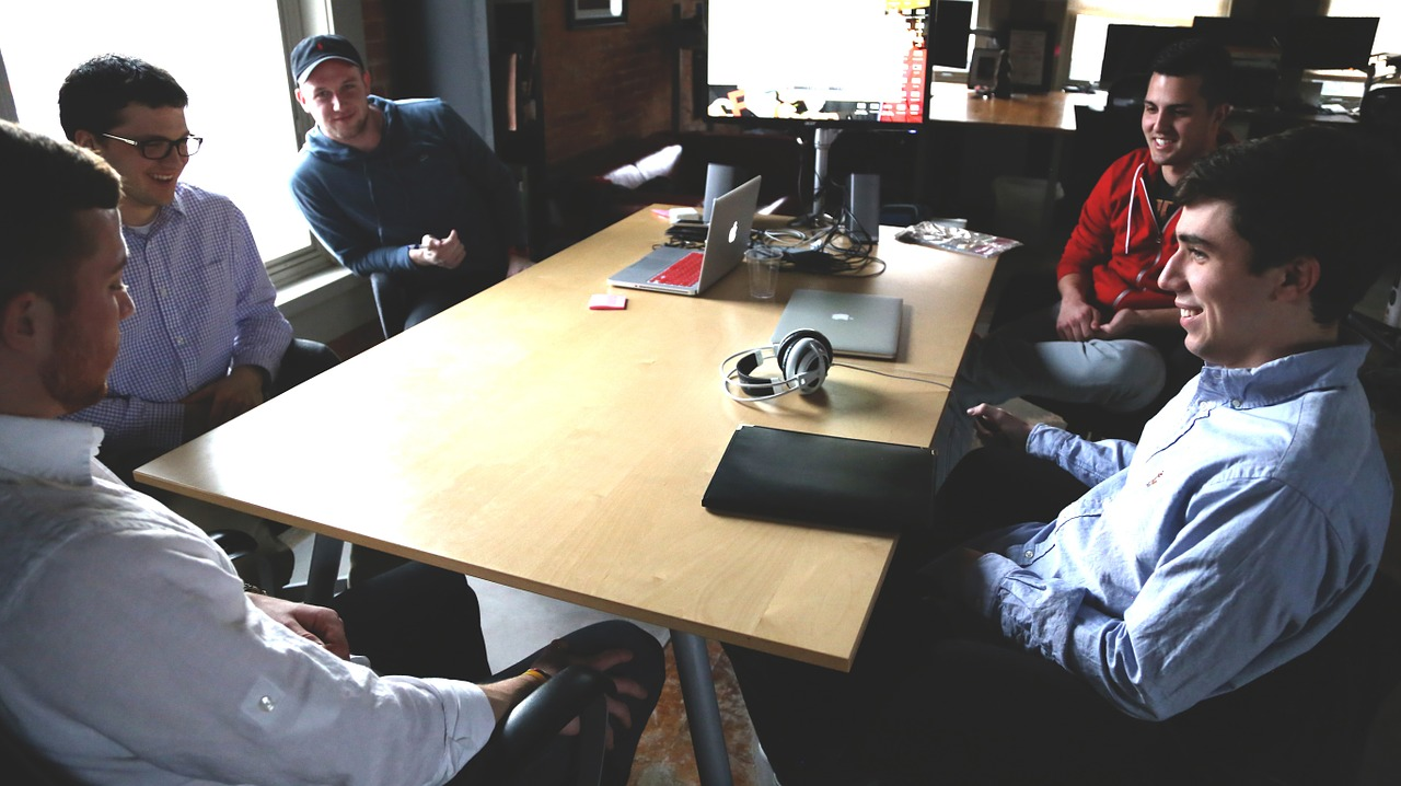 photograph picture of five men in office sitting around a table for meeting