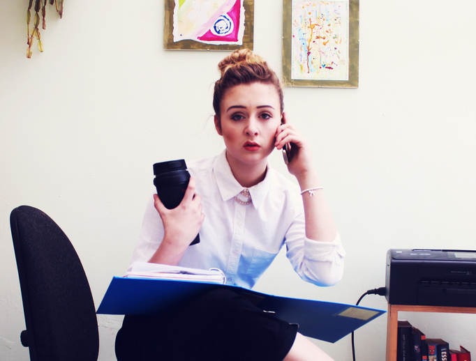photograph picture of a woman in an office on the phone