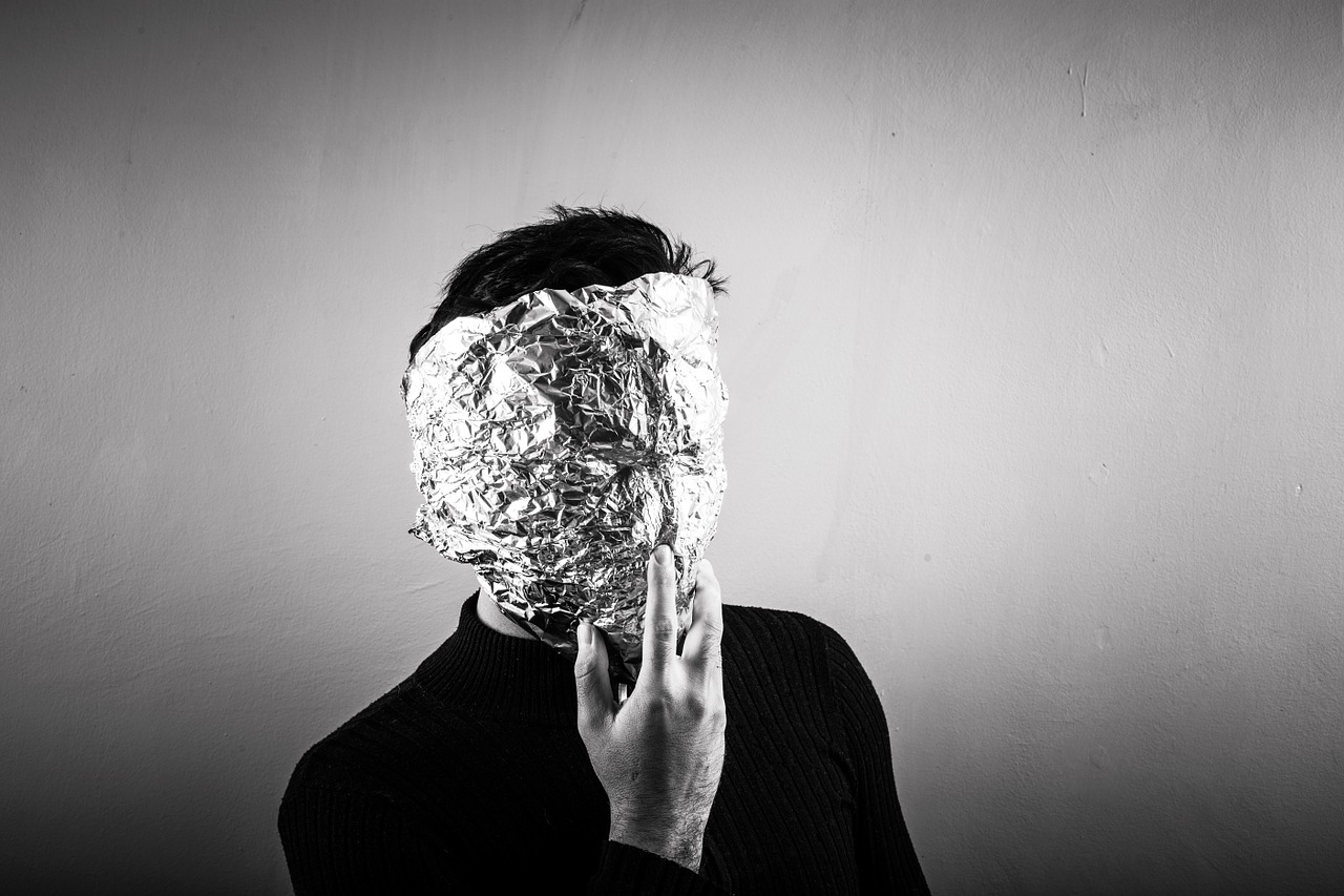 photograph picture of a man covering his face aluminium foliage anonymous