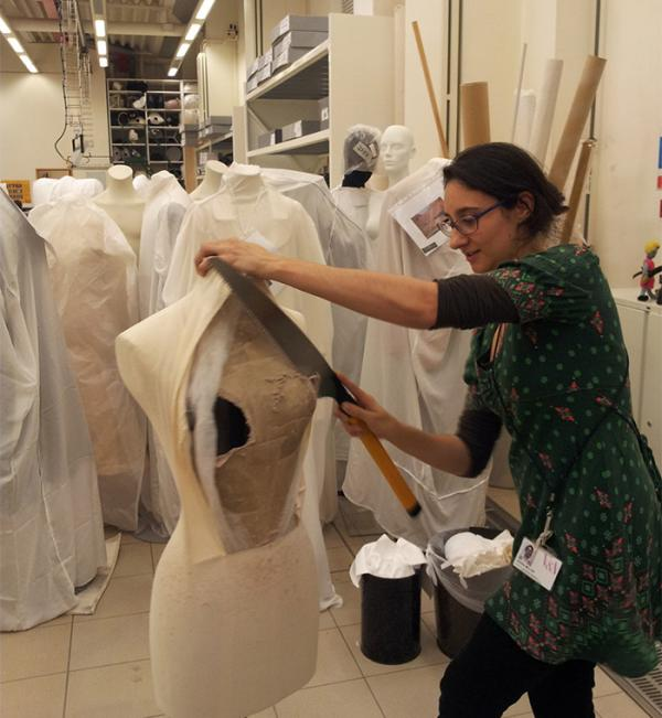 Costume Mounting Specialist Keira Miller removing the bust from a papier-mâché figure
