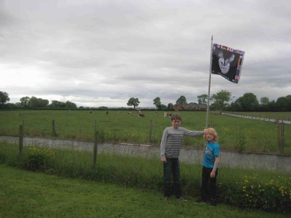 Two boys in Lough Neagh holding a G8 protest poster as a flag