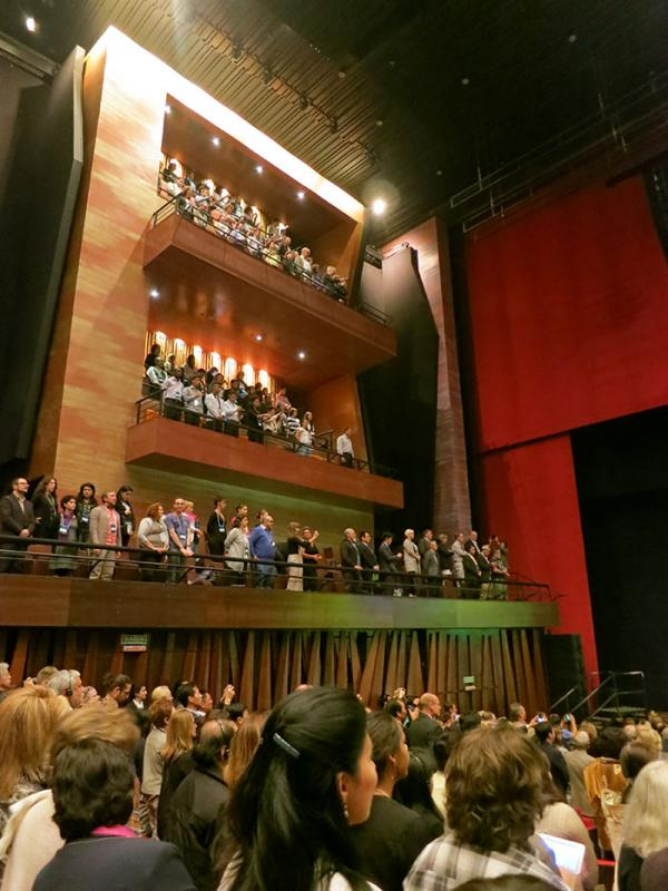 A packed theatre hall of museum professionals standing for the Brazilian national anthem