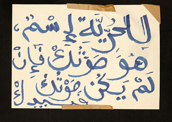 "Banner in Arabic: ""YOUR WAY TO FREEDOM IS YOUR VOICE. IF THAT'S NOT ENOUGH, THEN USE YOUR HAND"". Archivo 15M. CC"