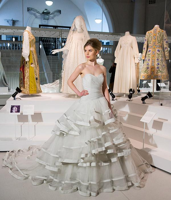 Jenny Bishop poses in an Ian Stuart wedding dress in front of one of the exhibition's displays. © Victoria and Albert Museum, London