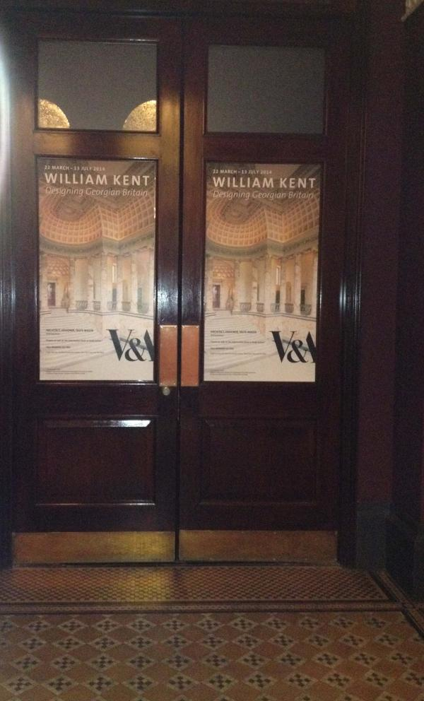 The doors to the V&A's exhibition space, with posters showing the entrance hall to Holkham.
